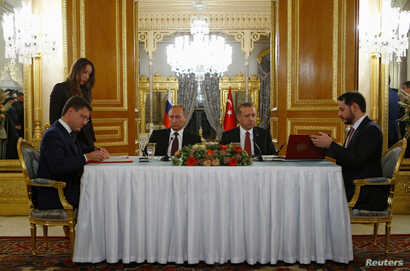 Russian Energy Minister Alexander Novak (L) and his Turkish counterpart Berat Albayrak sign an agreement in Istanbul, Turkey, Oct. 10, 2016.