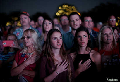 Supporters of Republican U.S. presidential nominee Donald Trump recite the Pledge of Allegiance at a campaign rally in Panama City, Florida, Oct. 11, 2016.