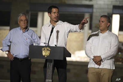 Venezuela's opposition leader Juan Guaido speaks flanked by Chile's President Sebastian Pinera, left, and Colombia's President Ivan Duque in front of a warehouse housing U.S. humanitarian aid destined for Venezuela, in Cucuta, Colombia, Feb. 22, 2019...