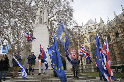 Anti-Brexit demonstrators wave flags outside the houses of Parliament in London, Britain, Dec. 19, 2018.