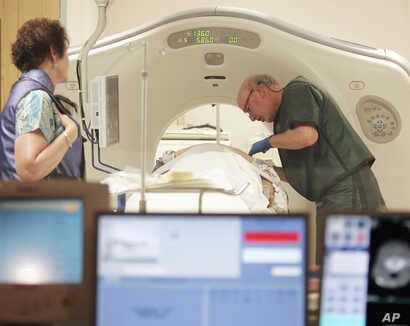 FILE - A physician uses a CT scanner to screen a patient for lung cancer at Southern New Hampshire Medical Center in Nashua, N.H., June 3, 2010.