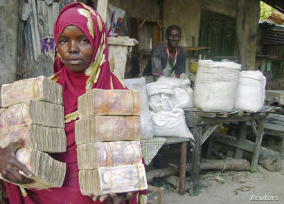 A moneychanger carrying Somali currency poses at an open air market in Mogadishu, Oct. 10, 2008.