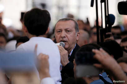 Turkish President Recep Tayyip Erdogan addresses the crowd following a funeral service for victims of the thwarted coup in Istanbul at Fatih Mosque in Istanbul, July 17, 2016.