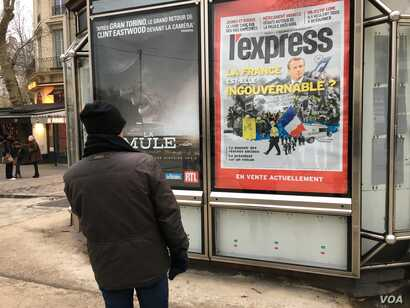 A Parisian looks at a newspaper billboard on France's current political dilemmas.