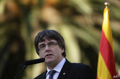 Catalan regional President Carles Puigdemont addresses to the media after a ceremony commemorating the 77th anniversary of the death of Catalan leader Lluis Companys at the Montjuic Cemetery in Barcelona, Spain, Oct. 15, 2017.