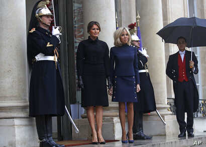 France's first lady Brigitte Macron and her U.S. counterpart Melania Trump stand on the steps of the Elysee Palace in Paris, France, Nov.10, 2018.