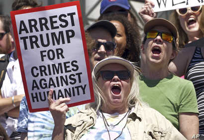 Activists hold signs to protest the Trump administration's approach to illegal border crossings and separation of children from immigrant parents, June 30, 2018, in Salt Lake City.