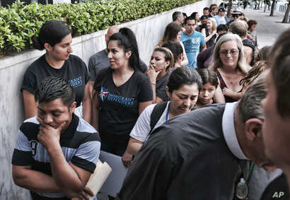 Hermelindo Che Coc, left, from Guatemala waits in line prior to a required check-in with immigration enforcement authorities in downtown Los Angeles, July 10, 2018. Che Coc says his 6-year-old son feared he was dead after U.S. authorities separated t...