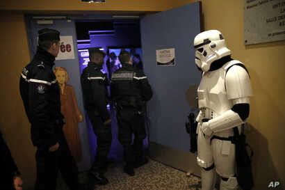 In this Feb. 10, 2019, photo, a man dressed up as Stormtrooper and French gendarmes watch a national lightsaber tournament in Beaumont-sur-Oise, north of Paris.