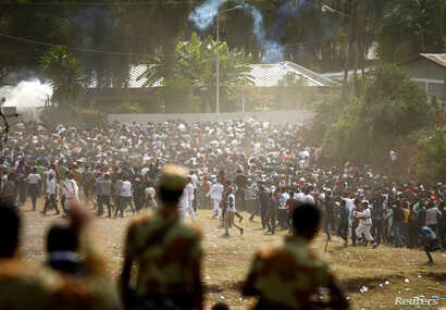 FILE - Protestors run from tear gas launched by security personnel during the Irecha, the thanks giving festival of the Oromo people in Bishoftu town of Oromia region, Ethiopia, Oct. 2, 2016.