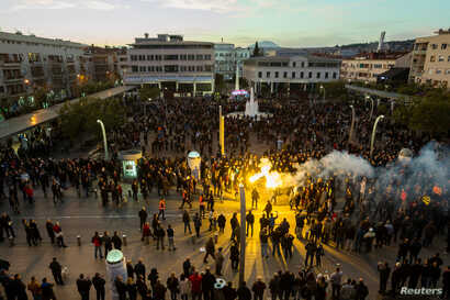 Protesters opposed to against longtime Montenegrin President MiloDjukanovic light flares in Podgorica, Montenegro, March 16, 2019.