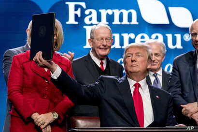 President Donald Trump holds up a signed executive order and a memorandum on rural broadband access at the American Farm Bureau Federation's Annual Convention Monday, Jan. 8, 2018, in Nashville, Tenn.