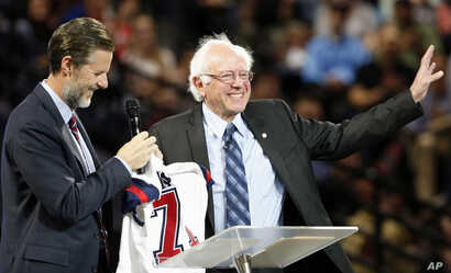 Democratic presidential candidate, Sen. Bernie Sanders, right, waves to the crowd after being presented with a shirt by Liberty President Jerry Falwell Jr., left, during a visit at Liberty University  in Lynchburg, Virginia, Sept. 14, 2015.