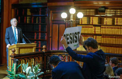 """An environmental activist holds a banner reading """"resist"""" while attending a speech by Myron Ebell, left, who leads U.S. President Donald Trump's Environmental Protection Agency's transition team, in Brussels, Belgium, Feb. 1, 2017."""