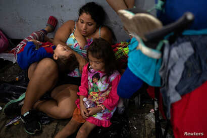 FILE - Tatiana, from El Salvador, sits with her children Michael Daniel, 3, and Maria Teresa, 5, amid a caravan of thousands of migrants from Central America taking a rest while en route to the United States, in Tapachula city center, Mexico, Oct. 21...