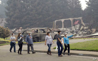 Carol Smith, far right in blue, her daughter Suzie Scatena, third from right, and husband Tim, third from left, tour their fire-ravaged neighborhood along with support crews, Aug. 2, 2018, in Redding, Calif. The Smiths' home of 30 years was destroyed...