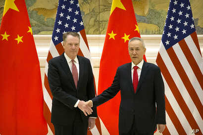 U.S. Trade Representative Robert Lighthizer, left, and Chinese Vice Premier and lead trade negotiator Liu He shake hands before the opening session of trade negotiations at the Diaoyutai State Guesthouse in Beijing, Feb. 14, 2019.