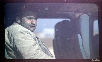 A man from the northern Syrian town of Ras al-Ain looks out from a bus window while being transported to a refugee camp, in the Turkish border town of Ceylanpinar, November 20, 2012.
