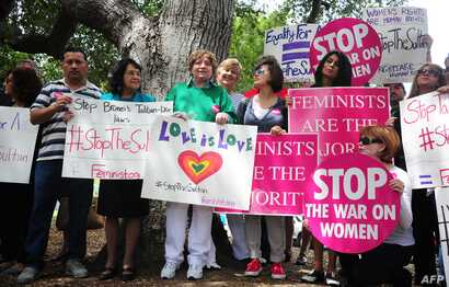 FILE - Supporters of Women's Rights and LGBT groups protest across from the Beverly Hills Hotel, owned by the Sultan of Brunei, demanding he rescind a Taliban-like Brunei penal code which included the stoning to death of gay men and lesbians and the ...