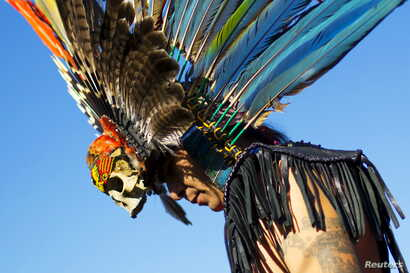 "A reveller gets ready to dance during a ""pow-wow"" celebrating the Indigenous Peoples Day Festival in Randalls Island, New York, October 11, 2015."