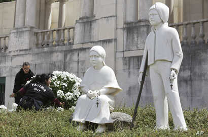 Two women set flowers by a statue of Jacinta and Francisco Marto at the Fatima Sanctuary, May 11 2017, in Fatima, Portugal. Pope Francis is visiting the Fatima shrine May 12-13 to canonize the two Portuguese shepherd children.