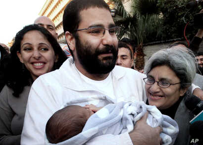 FILE - Egyptian prominent blogger Alaa Abdel-Fattah, center, hugs his recently born son, Khaled, his mother, Laila Soueif, right, and his sister, Ahdaf Soueif, left, after his release, in Cairo, Egypt.