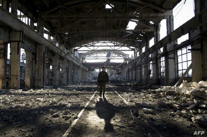 An Ukrainian serviceman walks through the rubble of a destroyed workshop after fighting with pro-Russian separatists in Avdiivka, Donetsk region, March 31, 2017.