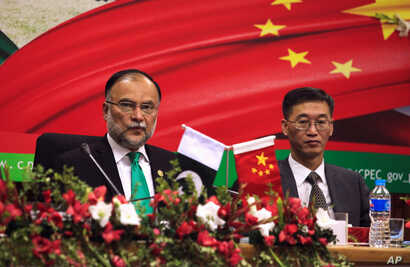 FILE - Ahsan Iqbal (L), Pakistan's Minister of Planning and Development and Yao Jing, Chinese Ambassador to Pakistan attend the launching ceremoney of CPEC long-term cooperation plan in Islamabad, Pakistan December 18, 2017.