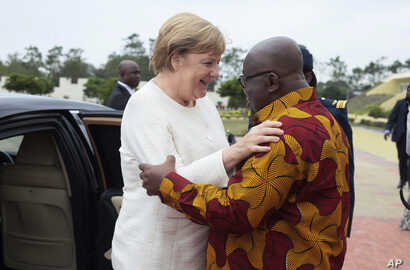 German Chancellor Angela Merkel, left, is welcomed by Ghana's President, Nana Akufo-Addo, right, at the Presidential palace in Accra, Ghana, Aug 30, 2018.