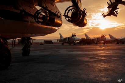 In this Russian Defense Ministry Press Service photo, a Russian Su-25 ground attack jet is parked at Hemeimeem air base in Syria, with Su-24 bombers seen in the background, Dec. 18, 2015.