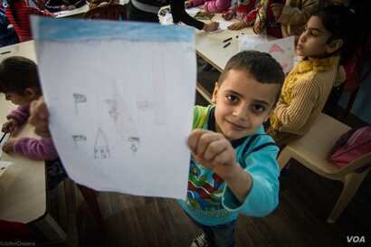 A child shows off his latest drawing as part of a class run by NGO Najda Now. The classes allow refugee children the chance to depict their dreams and fears through pictures, Dec. 4, 2015. (J. Owens/VOA)