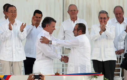 Colombia's President Juan Manuel Santos, front left, and the top commander of the Revolutionary Armed Forces of Colombia (FARC) Rodrigo Londono, known by the alias Timochenko, shake hands after signing the peace agreement between Colombia's gover...