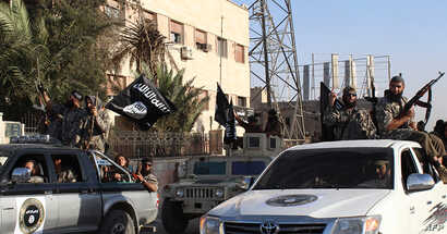An image made available by Jihadist media outlet Welayat Raqa on June 30, 2014, allegedly shows a member of the IS (Islamic state) militant group parading in a street in the northern rebel-held Syrian city of Raqqa.