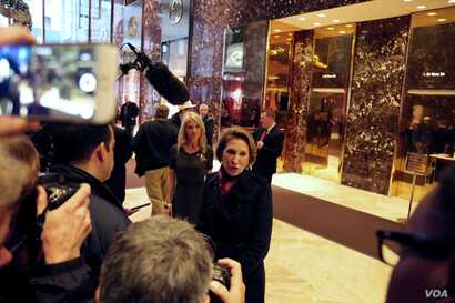 A slew of shutters clicks as Former Hewlett-Packard CEO and Republican presidential candidate Carly Fiorina walks through the lobby at Trump Tower in New York, Dec. 12, 2016. (R. Taylor/VOA)