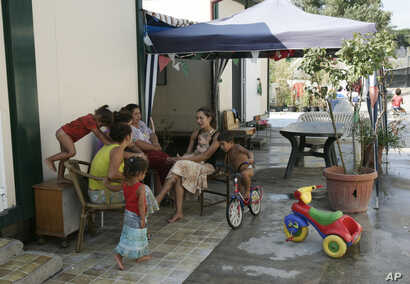 Women sit and talk while children play at a Gypsy camp in Rome, Aug. 6, 2008.