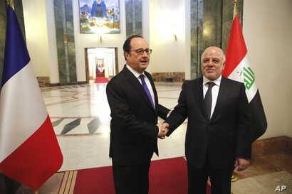 Iraq's Prime Minister Haider al-Abadi, right, greets French President Francois Hollande prior to their meeting in Baghdad, Iraq, Jan. 2, 2017.