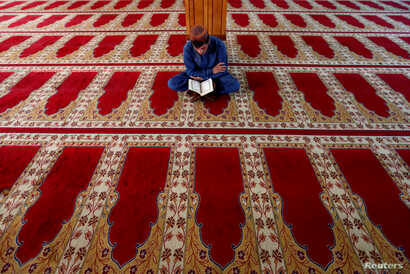 An Afghan man reads the Quran at a mosque on the first day of the holy month of Ramadan in Kabul, Afghanistan, May 27, 2017.