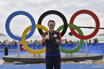 Triathlete Gwen Jorgensen of the United States poses with her gold medal at the 2016 Summer Olympics in Rio de Janeiro, Aug. 20, 2016.