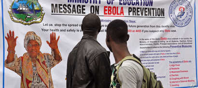The image of Liberia President Ellen Johnson Sirleaf, left, appears on a public information banner warning people about the Ebola virus in the city of Monrovia, Aug. 8, 2014.