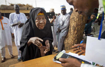FILE - An elderly Nigerian woman is seen participating in elections in Daura, Nigeria, March 28, 2015.