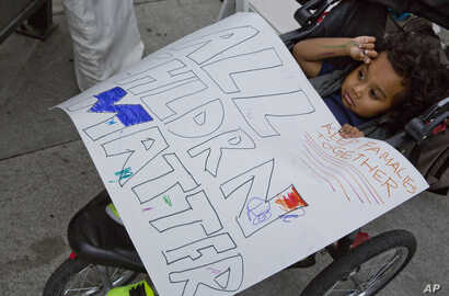 Owen Munoz, 2, holds a sign as his mother, Mia, joins a group protesting the separated of immigrant families caught on the southwest border near San Diego, Calif., as the group rallies at the federal building in Los Angeles, June 23, 2018. More than ...