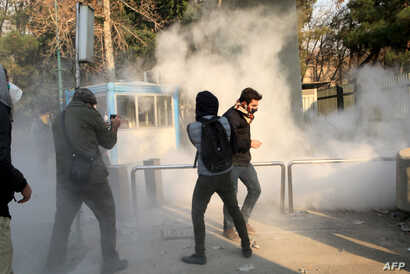 Iranian students run for cover from tear gas at the University of Tehran during a demonstration driven by anger over economic problems, in the capital Tehran, Iran, Dec. 30, 2017.