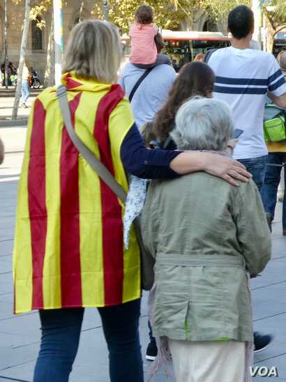 A guiding hand: grand-daughter and grandmother make their way to join a pro-independence rally Sunday in Barcelona.