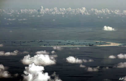 FILE - This aerial photo taken through a glass window of a military plane shows China's alleged on-going reclamation of Mischief Reef in the Spratly Islands in the South China Sea, May 11, 2015.