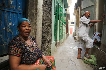 Residents emerge from their homes after Comoros armed forces members clear the medina of weapons and armed men at Mutsamudu, Oct. 20, 2018, on the island of Anjouan.