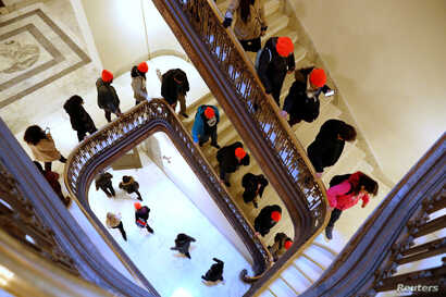 """Demonstrators calling for new protections for so-called """"Dreamers,"""" undocumented children brought to the U.S. by their immigrant parents, walk through a Senate office building on Capitol Hill in Washington, Jan. 17, 2018."""