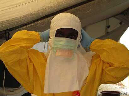 Health care workers' protective gear can look frightening. Here, a worker prepares to care for Ebola patients at the Doctors Without Borders treatment unit at Donka hospital in Conakry, Guinea.