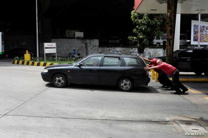 Attendants push a car at a gas station of Venezuelan state-owned oil company PDVSA in Caracas, Venezuela, Sept. 21, 2017.