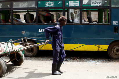 A man pulling a cart passes next to a bus vandalized during the latest protests in Mathare, Nairobi, Kenya, August 14, 2017.