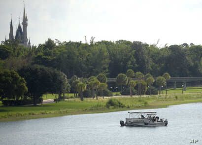 Orange County Sheriff's officers search the Seven Seas Lagoon between Walt Disney World's Magic Kingdom theme park, left, and the Grand Floridian Resort & Spa in Lake Buena Vista, Florida, June 15, 2016, after a two-year-old toddler was dragged into ...